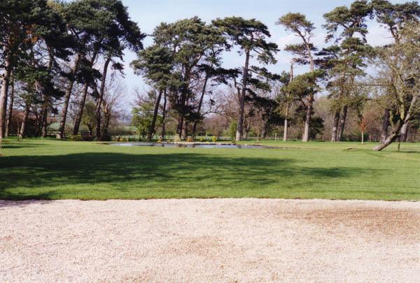 Large concrete pond set in a lawn